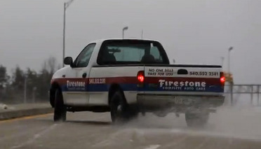 Define Irony: Tire Truck Sliding All Over Road in Snow Storm