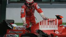 Räikkönnen inspects damage to his Ferrari